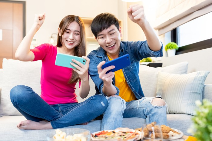 A couple plays smartphone games on the couch.