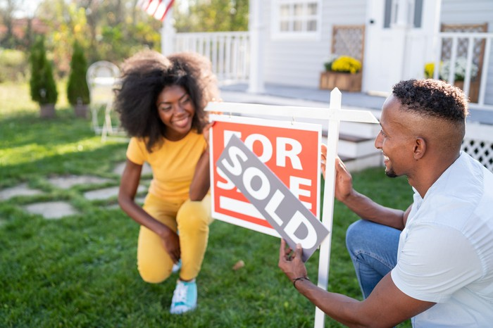 Young couple changing For Sale sign in yard to Sold