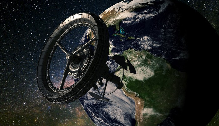 """Large ring space station over Earth with stars in background  -  url https 3A 2F 2Fg - Why This Space Expert Thinks """"Hundreds of Thousands of Humans"""" Could Live in Space By 2050"""