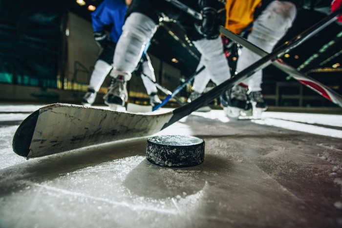 Ice-level view of the puck and players in a hockey game.