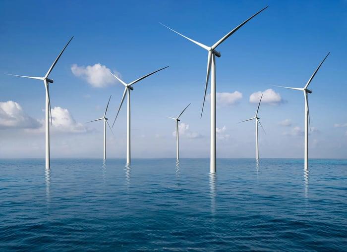 Des rangées de moulins à vent en mer.