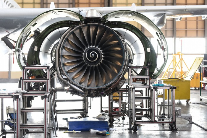 An aircraft's jet engine being repaired in a facility.