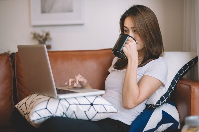 Woman sips coffee as she uses her laptop while lounging on her couch.