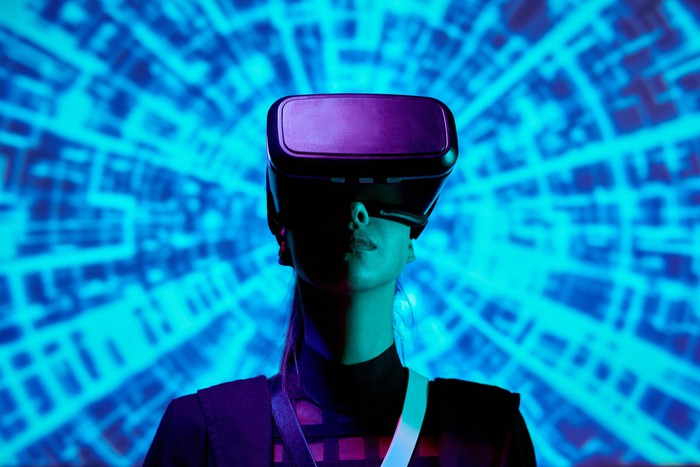 Woman wearing VR headset with digital background.