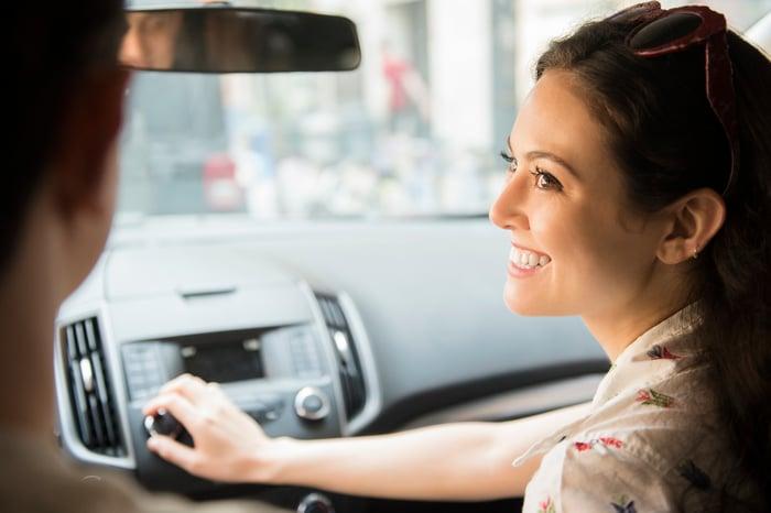 A smiling woman adjusts the car radio.
