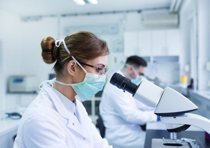 A scientist in white coat and surgicsl mask looks into a microscope.