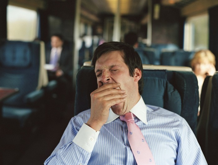 A businessman yawns while sitting in a seat on a train.