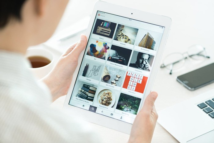 Woman's hands holding a white tablet showing various Pinterest categories.