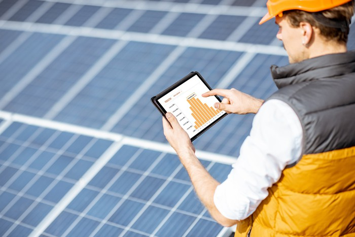 solar panel worker on roof assessing data on computer