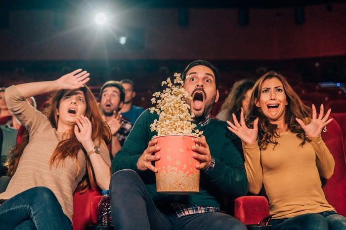 People in movie theater looking surprised