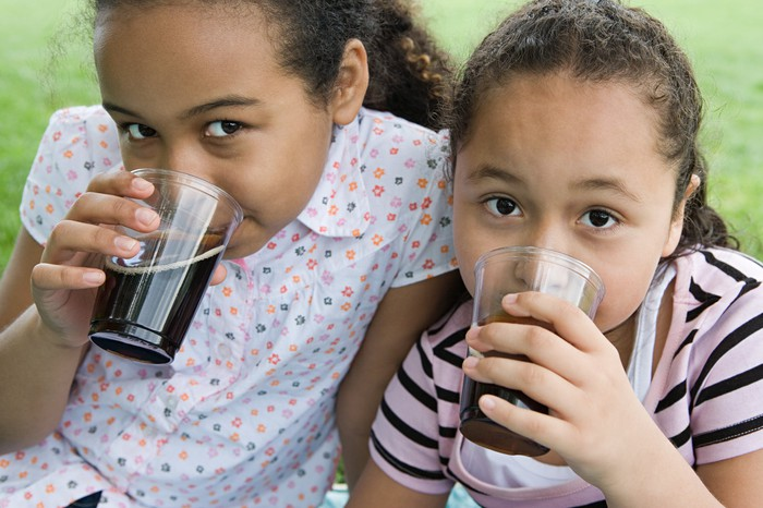 Two little girls drinking cola.