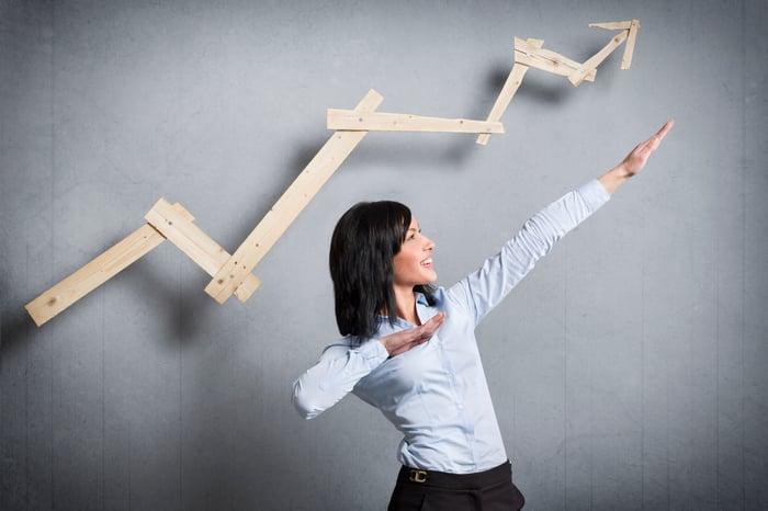 A woman gesturing upward while standing below an arrow trending upward, both implying growth.