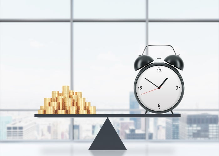 A scale balancing an alarm clock and a pile of gold coins.