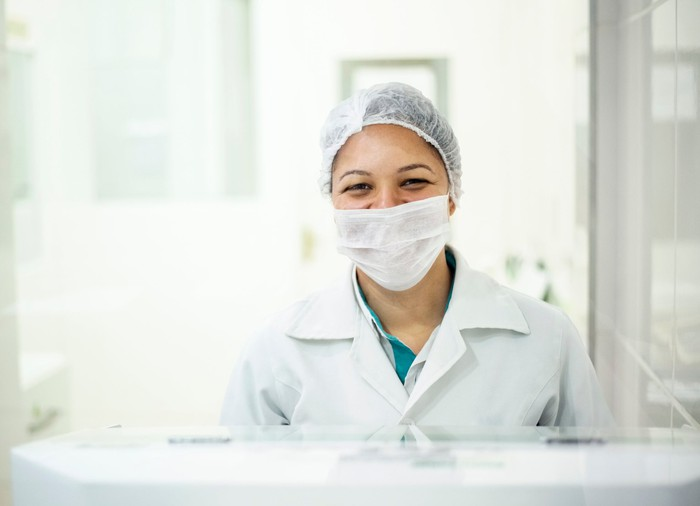Female medical scientist smiles from behind a mask in a pharmaceutical lab.