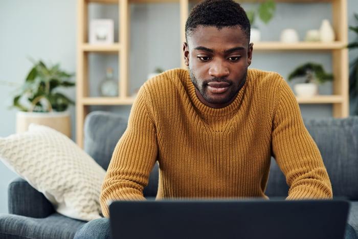 Un homme assis sur un canapé avec un ordinateur portable ouvert devant lui.