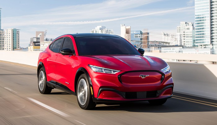A red Ford Mustang Mach-E, a sporty electric crossover SUV, on a city highway