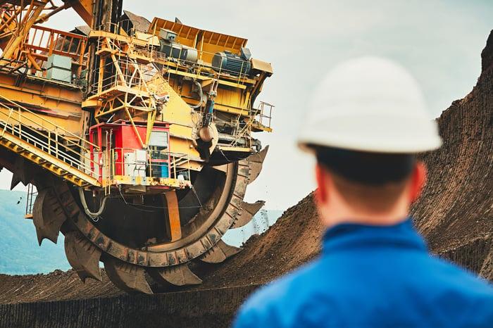 A man watching a coal mining machine.