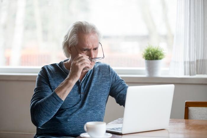 Shocked senior man removing glasses to stare at laptop