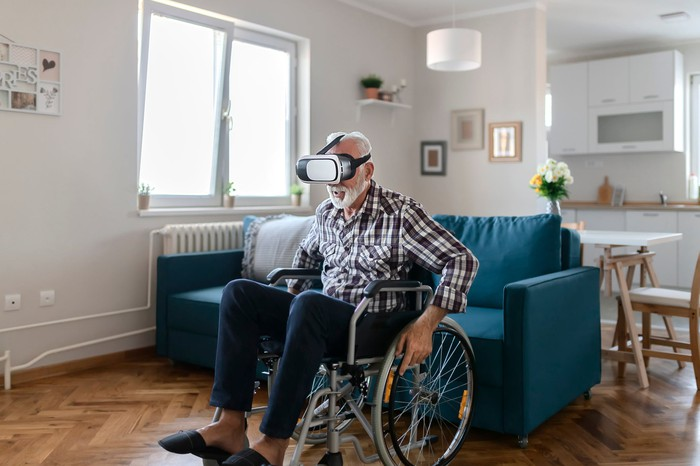 Man in wheelchair uses virtual reality device at home.