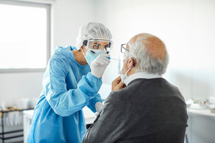 A clinician in full-body protective equipment administering collecting a throat swab to test for influenza.
