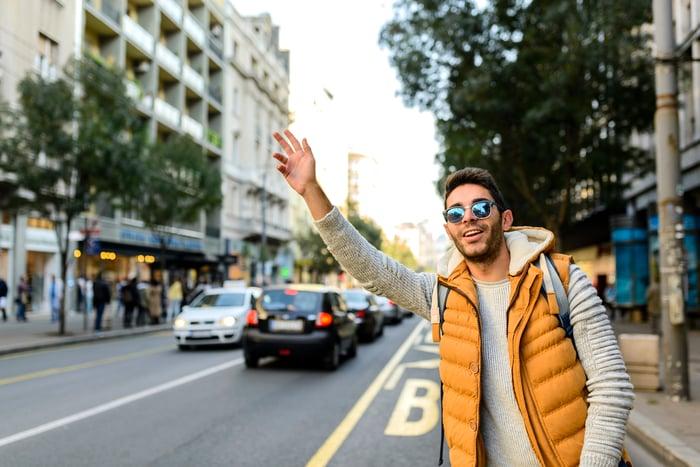 A man in a vest hailing a car