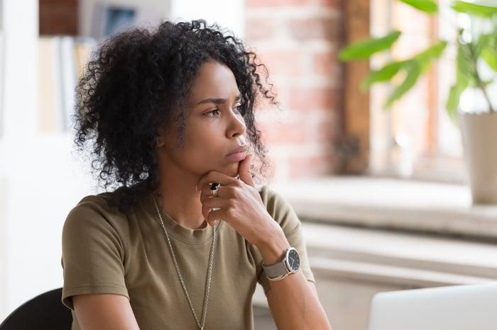 Une femme regardant par la fenêtre, la main sur le menton, réfléchissant à une question.