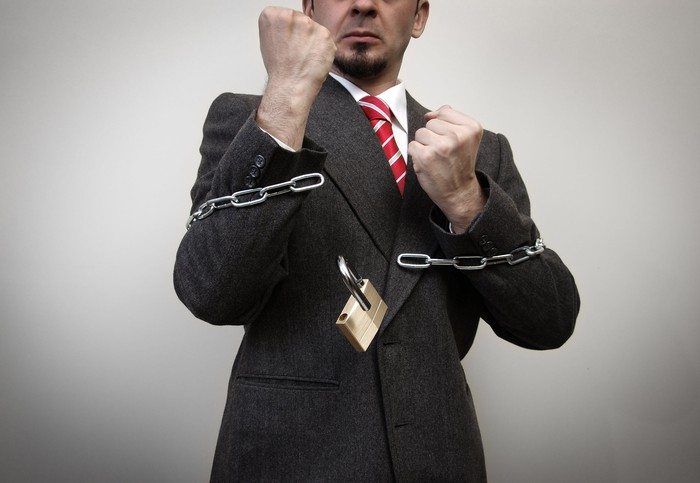 A businessman with fists raised is breaking free of chains.