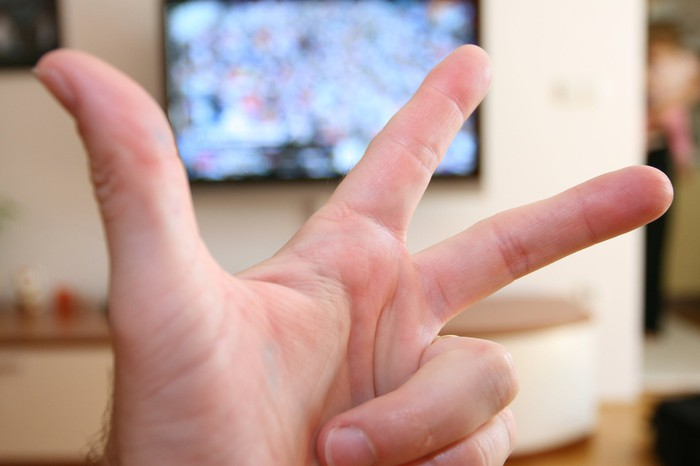 A hand holds up three fingers with a television in the background