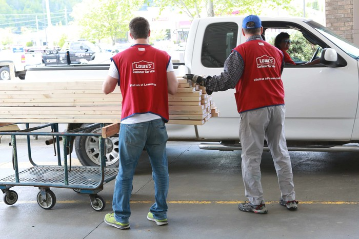 Two Lowe's employees loading some wood into a customer's white pickup truck.