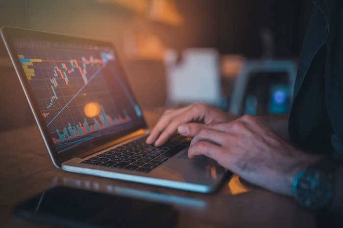 A person looking at a rising candlestick chart on their laptop monitor.