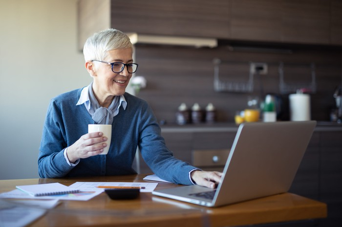 Mature woman sits at a table in front of her laptop, with a cup of coffee in hand.