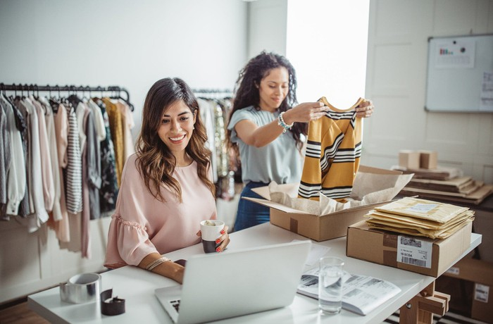 Two business owners fold clothes as they fill online orders.