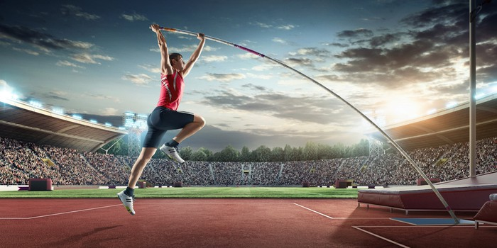 A man pole-vaults in front of a crowd in a stadium.