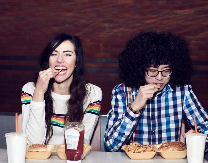 two people eating burgers and fries.