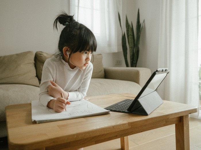A young girl attends an online class on her tablet.