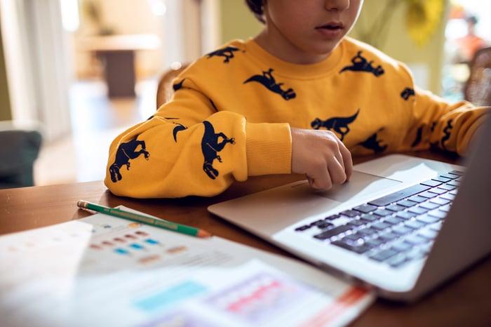 A child attends an online class on a laptop.