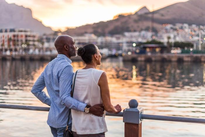 Un homme et une femme debout près de l'eau.