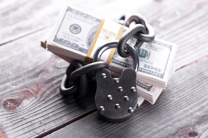A chain and lock wrapped around a stock of money, sitting on wooden 2x4s.