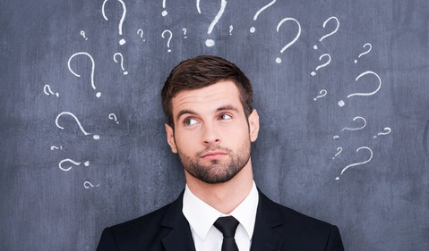 confused-looking man wearing suit and tie with question marks above his head -- thinking wondering what to do