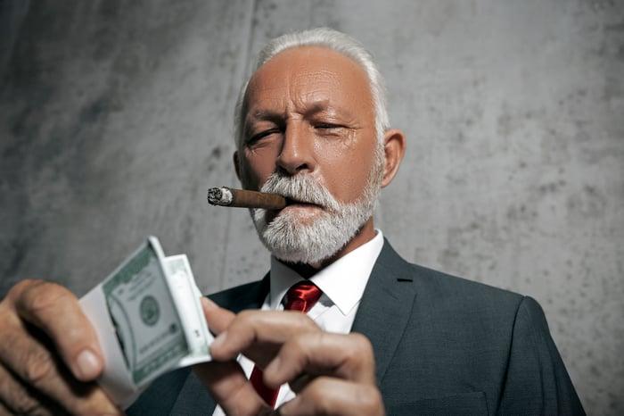 Homme âgé bien habillé comptant de l'argent et fumant un gros cigare.