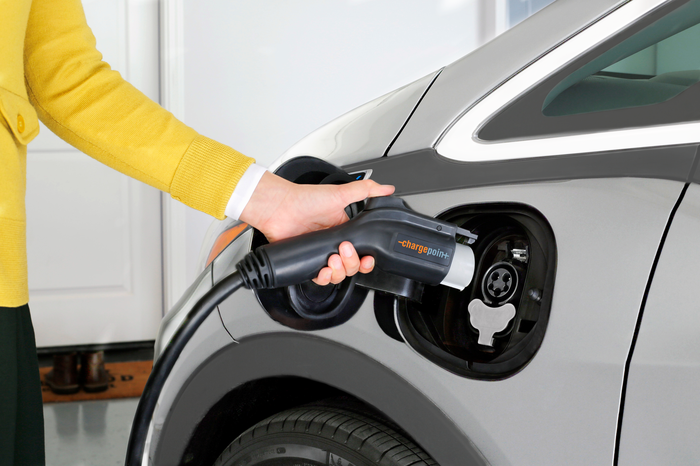 Woman charging electric car with ChargePoint charger