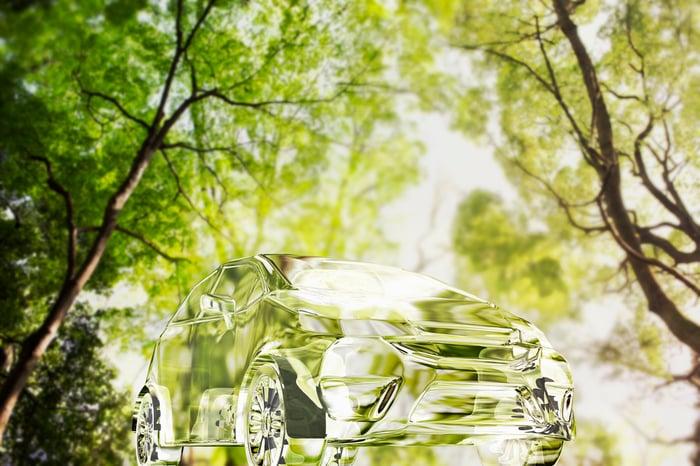 Transparent car among green trees