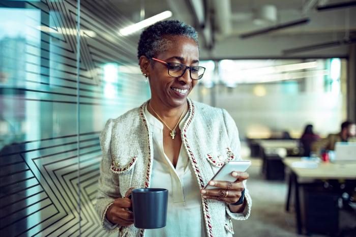 Senior woman looking at phone, tenant une tasse de café, souriant.