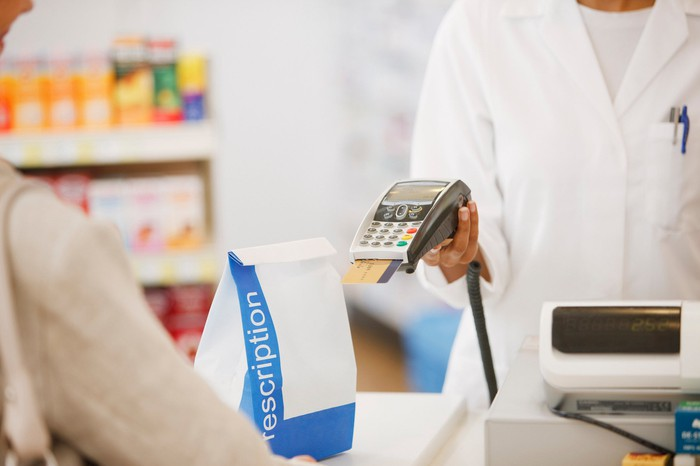 A pharmacist completing a payment card purchase at a pharmacy.