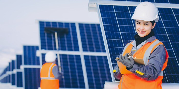 Two workers wearing hard hats standing next to solar panels