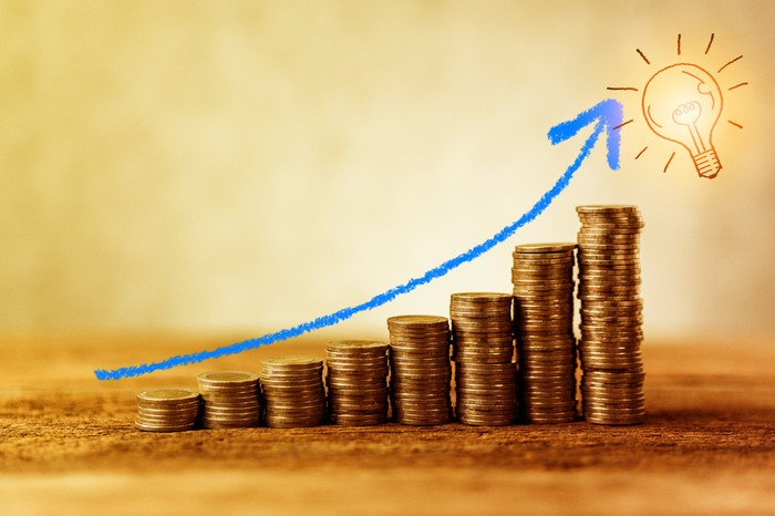 A rising arrow over a stack of coins, depicting income growth.