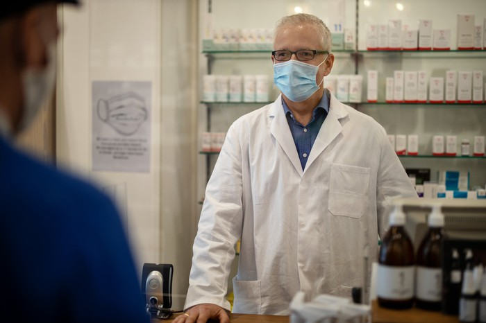 An older man in a white coat and mask standing at a pharmacy counter.