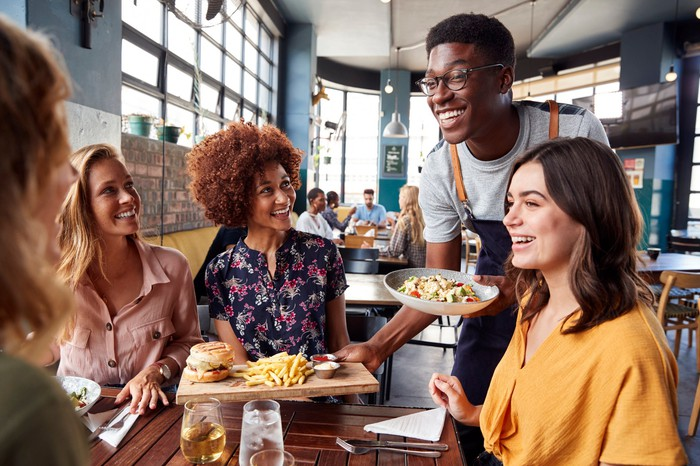A restaurant server bring food to a table of happy customers.