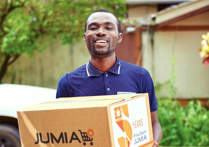 A man in Nigeria holds a box from Jumia.