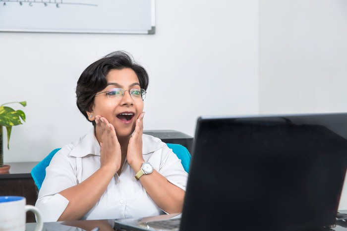 A woman is happily surprised by what she sees on a computer.